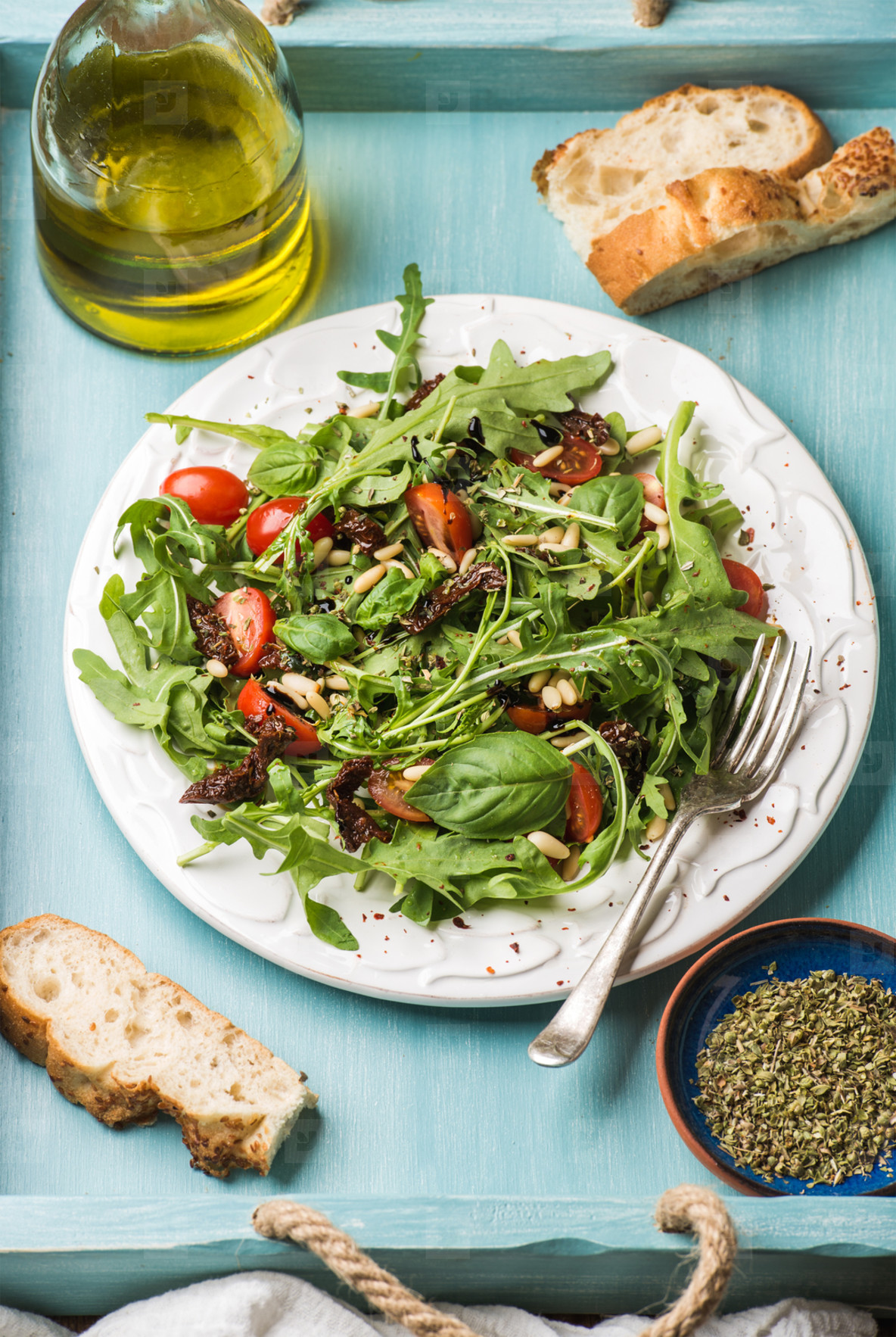 Salad with arugula  cherry tomatoes  pine nuts and herbs on white ceramic plate over blue wood background