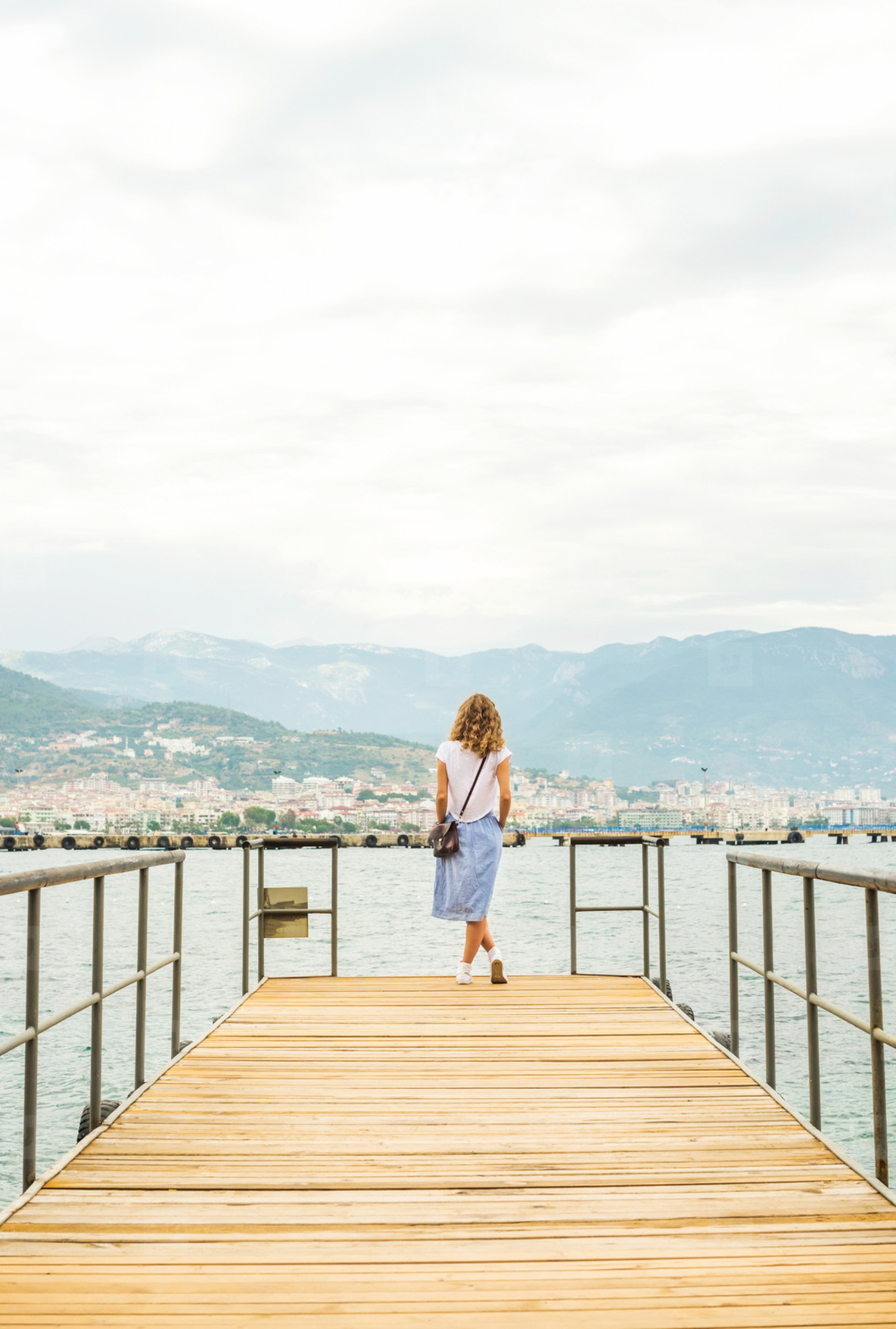 Young woman walking along pier
