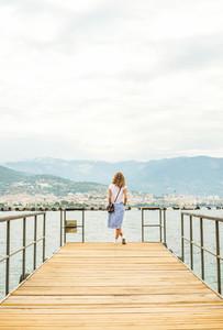 Young woman walking along pier