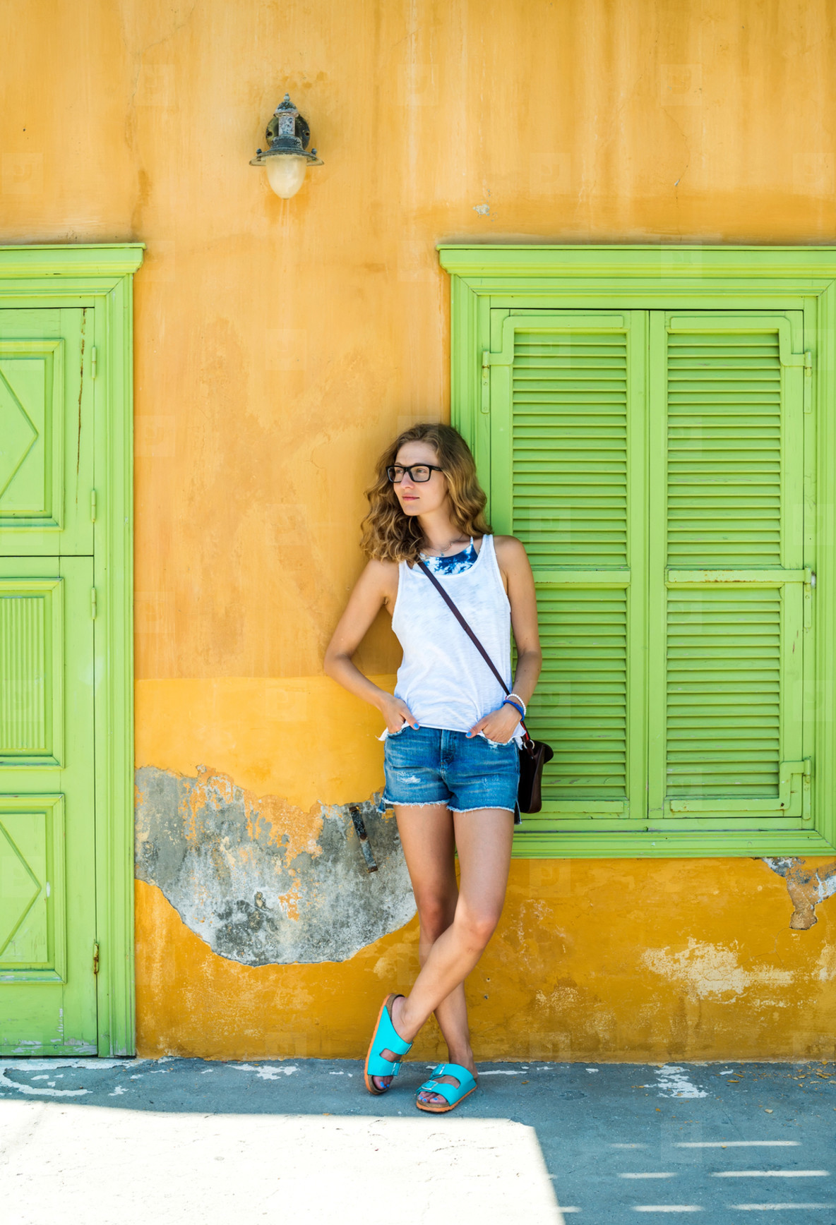 Young blond woman in typical Greek town with colorful buildings on Kastelorizo Island  Greece