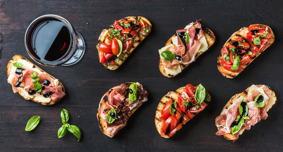 Brushetta snacks for wine Variety of small sandwiches on dark rustic wooden backdrop
