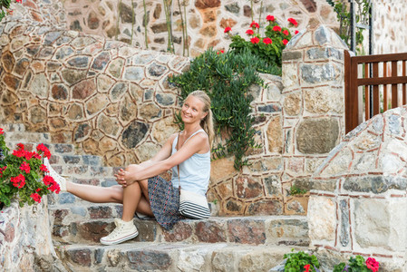 Young blond woman tourist sitting on stone stairs in the old town center of Alanya
