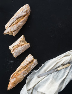 French baguette broken into pieces  white kitchen towel and vint