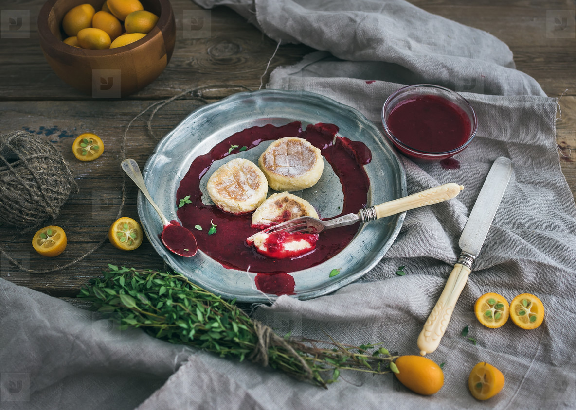 Rustic breakfast set  Russian cheese cakes on a vintage metal plate with lingonberry jam  fresh kumquats  thyme  decoration rope and old dinnerware over rough wooden desk