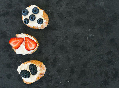 Goat cheese and berries mini sandwitches on a dark stone backgro