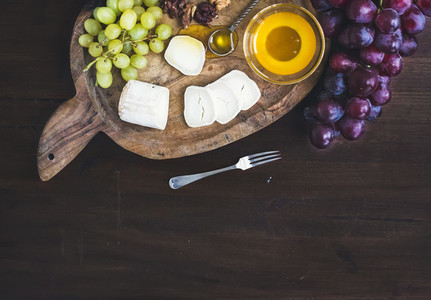 Goat brie cheese with fresh greapes and honey on a rustic wooden