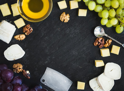 Cheese selection with fresh grapes  walnuts and honey on a dark
