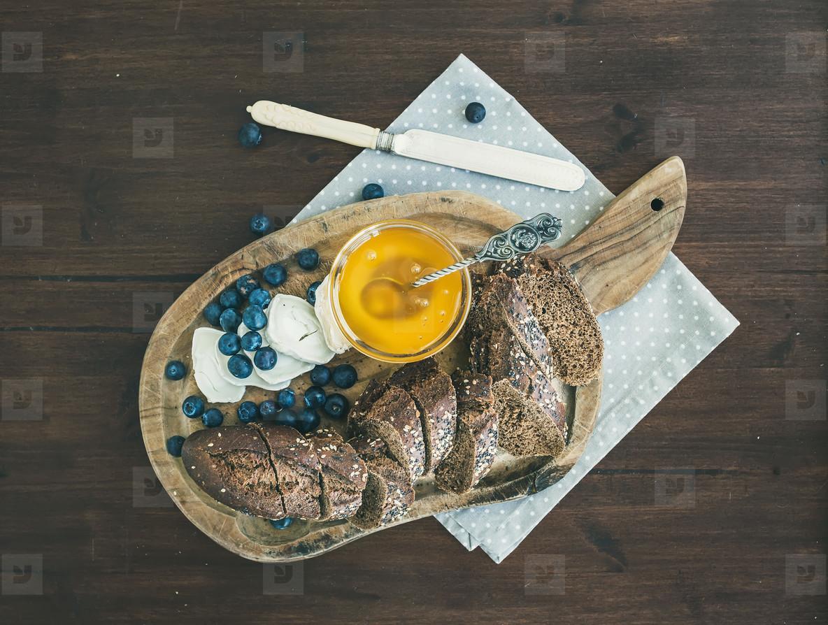 Breakfast set on a dark wood background  fresh dark baguette cut