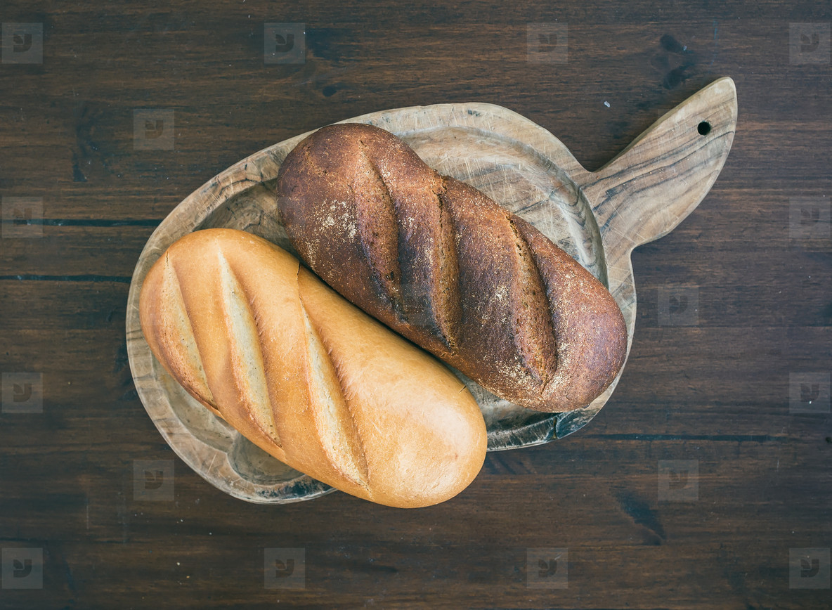 White and dark bread loafs on a rustic wooden board