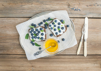 Healthy breakfast set with ricotta fresh blueberries honey and