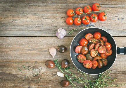 Roasted cherry tomatoes with garlic and thyme in a cooking pan o