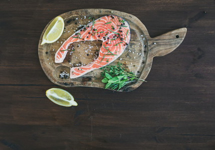 Raw salmon steak with fresh herbs  lemon and spices on rustic wo