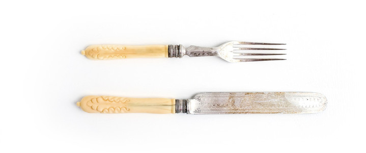 Set of vintage dinnerware Knife and fork with bone handles on a white background Top view