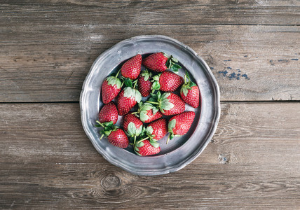 An old vintage metal plate full of fresh ripe strawberries over