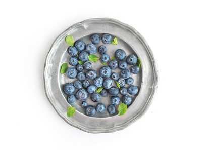 An old vintage metal plate full of fresh ripe blueberries over a