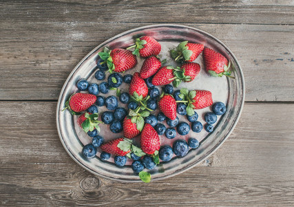 Fresh strawberry and blueberry mix on a metal dish tray over a