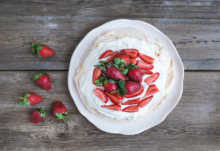 Rustic Pavlova cake with fresh strawberries and whipped cream ov