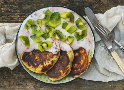 Rustic breakfast set with fluffy pancakes with strawberry yogurt