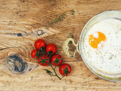 Breakfast set fried egg and cherrytomato on a wooden desk