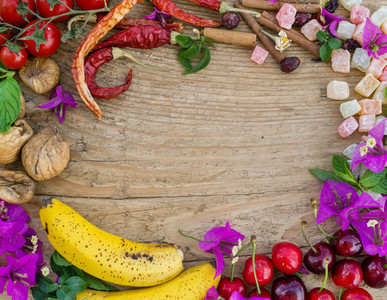 Mediterranean fruit  vegetables and flowers on a rough wooden bo