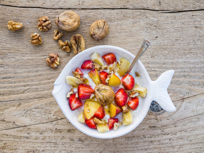 A bawl of fruit  walnuts and yogurt