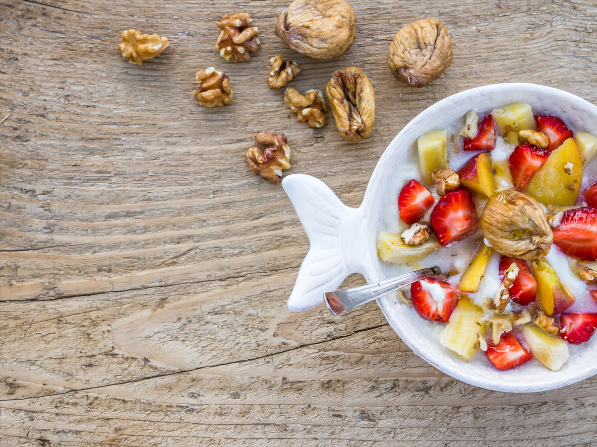 A bawl of fruit  walnuts and yogurt