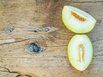 Two pieces of melon on a wooden background
