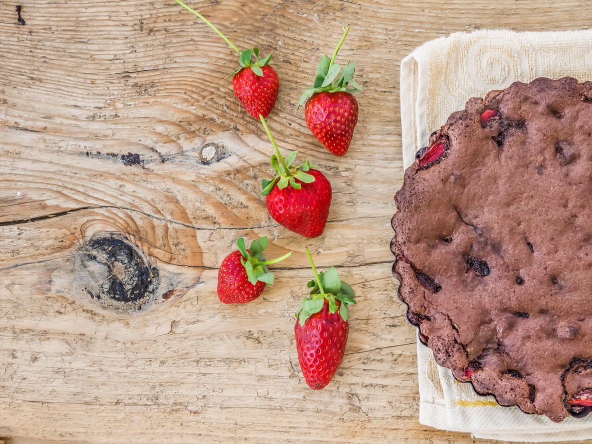Chocolate strawberry cake with fresh strawberries on a kitchen t
