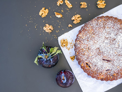 Plum cake with walnuts on white paper over a black background