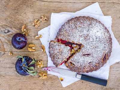 Plum cake with walnuts and fresh ripe plums on white paper over