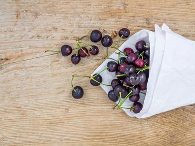 Paper bag of sweet cherries ona rough wood background