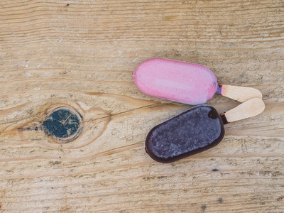 Two ice creams on a wooden board