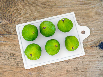 Fresh green figs on a white ceramic board over a black backgroun