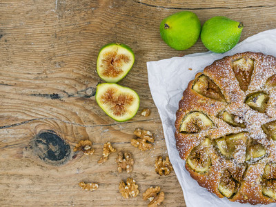 Fig pie with walnuts on a wooden desk