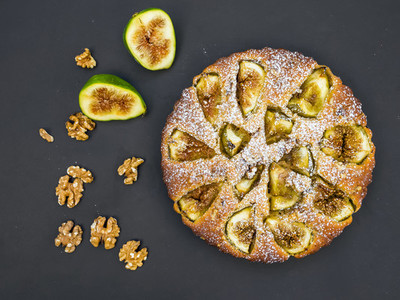 Fig cake with fresh figs and walnuts on black