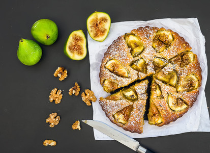 Fig pie with fresh figs and walnuts on black