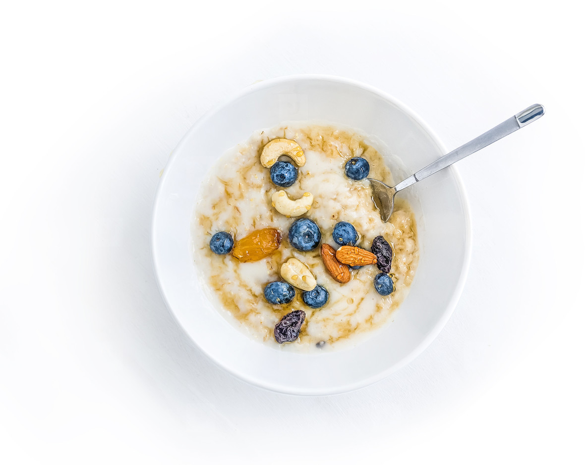 Oat porridge with fresh blueberry  nuts and honey in a white cer