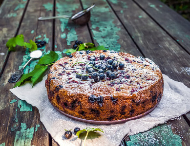 Black currant cake on a beige linen fabric over the old painted