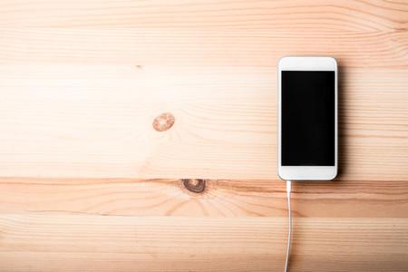 Blank smart phone on wood grain