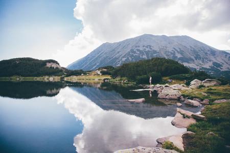 Girl next to a mountain lake