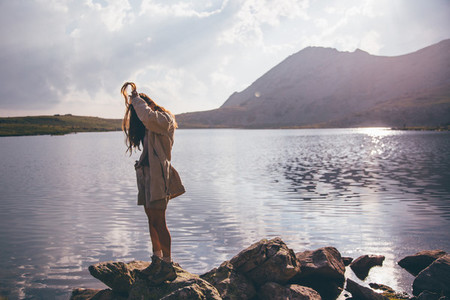 Girl looking at a mountain lake