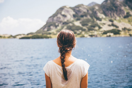 Girl looking at a mountain lake