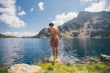 Young man near a mountain lake