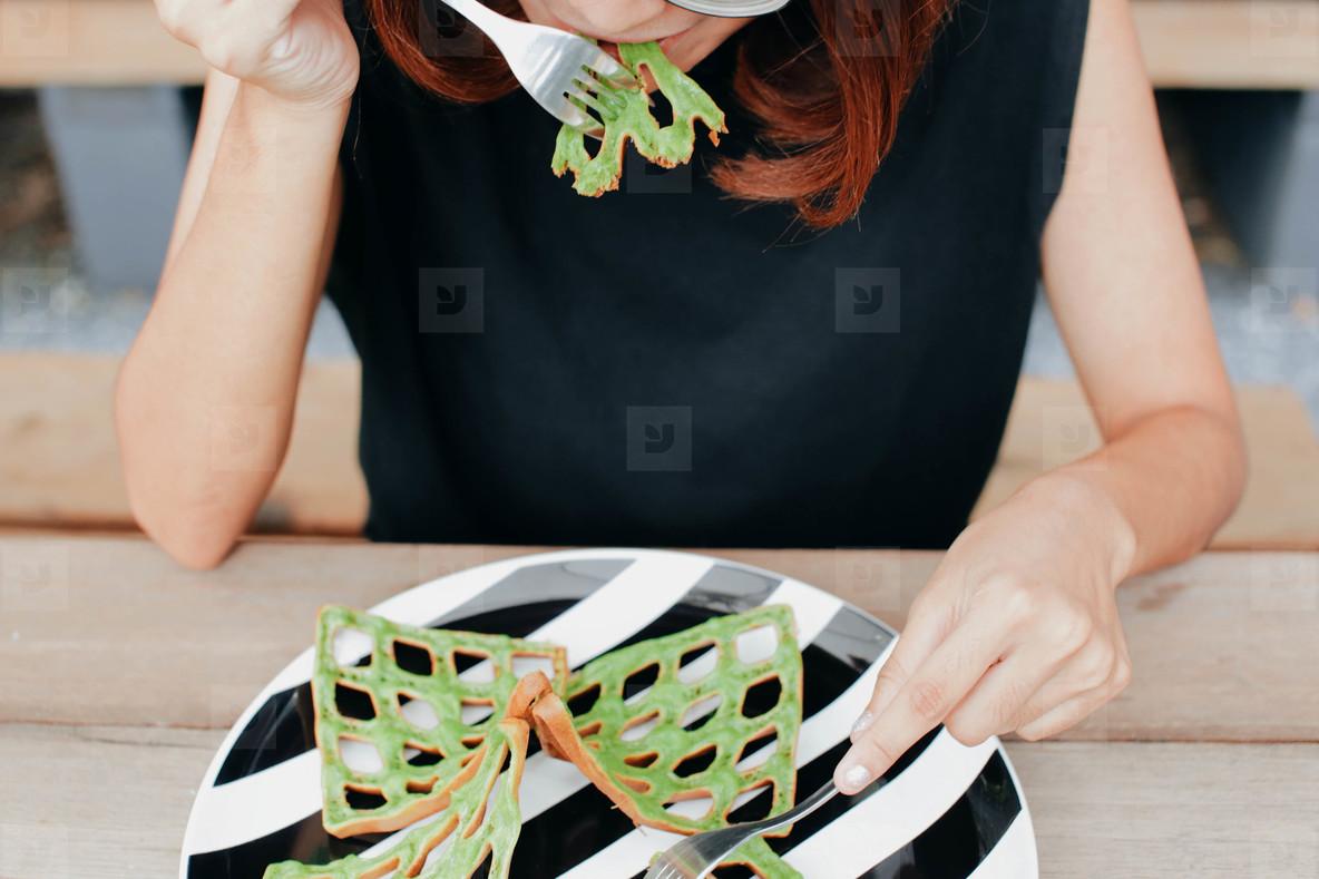Young girl eating matcha waffle