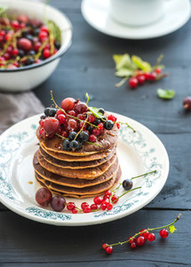 Breakfast set  Buckwheat pancakes with fresh berries and honey on rustic plate over black wooden table