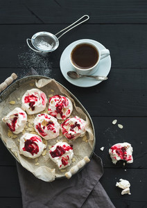 Raspberry and almond meringues with cup of coffee on black rustic wooden table  top view