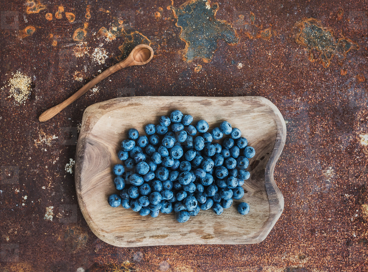 Blueberries in a rustic wooden serving dish over grunge metal rusty background