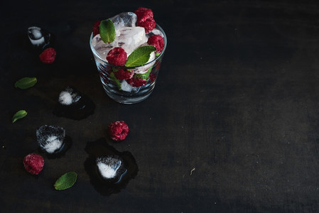 Ice cubes with mint leaves and raspberry in glass on dark grunge surface