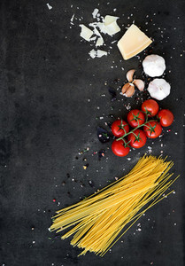 Food frame  Pasta ingredients  Cherry tomatoes  spaghetti pasta  garlic  basil  parmesan and spices on dark grunge backdrop  copy space