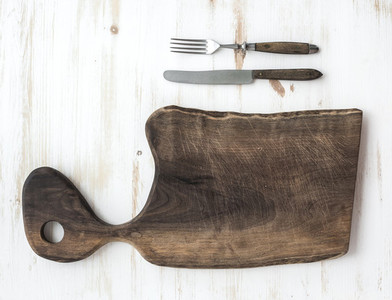 Kitchen ware set Old rustic chopping board made of walnut wood knife fork on a white background